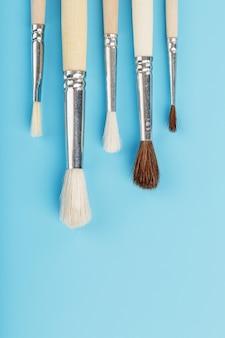 Pinceaux pour dessiner avec des peintures en bois naturel et laine sur fond bleu.