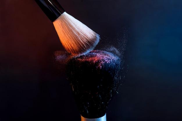 Pinceaux pour le maquillage avec de la poudre sur fond sombre