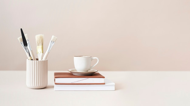 Pinceaux et tasse sur des livres