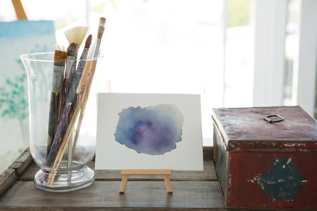 Pinceaux, toile et boîte sur table en bois