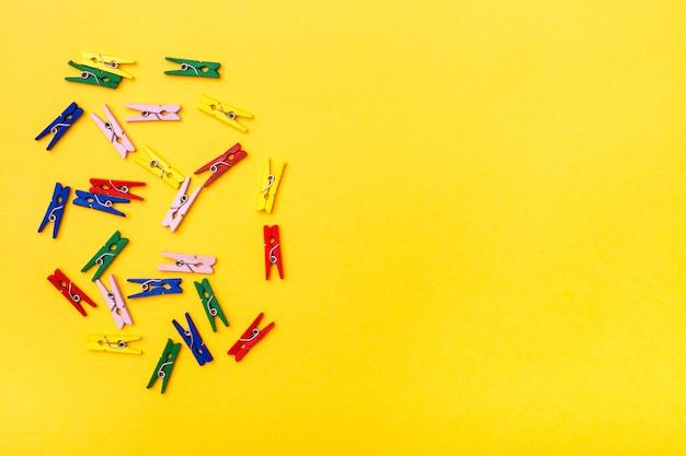 Des pinces en bois multicolores reposent de manière chaotique sur un fond jaune