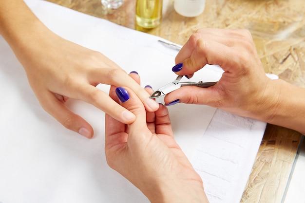 Pinces à cuticules dans les mains de femme