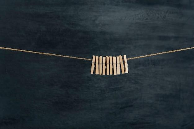Des pinces à linge en bois dans une corde attendent les vêtements après la lessive. mur noir à la surface.