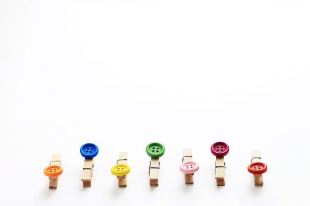 Pinces à linge en bois décoratifs avec des boutons aux extrémités.