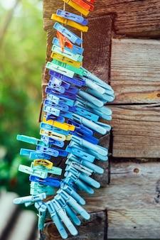 Pinces à linge colorées sur corde à linge sur fond de mur en bois