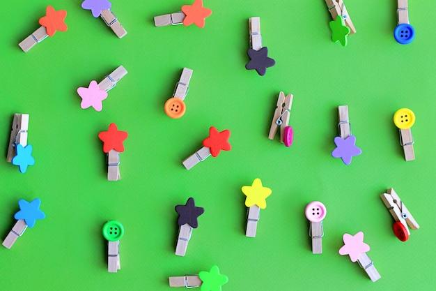 Pinces à linge décoratifs multicolores pour vêtements sur motif de fond vert
