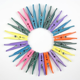 Pinces à linge en plastique de couleur pour vêtements sur une surface blanche
