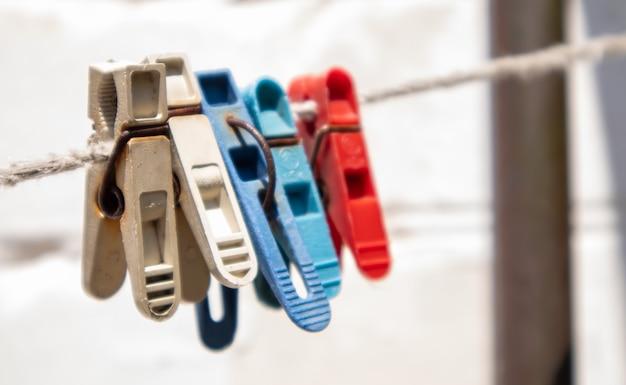 Des pinces à linge en plastique sont accrochées à la corde. corde à l'extérieur, sur un arrière-plan flou dans un jardin ensoleillé. corde à linge dans la rue. pinces à linge.