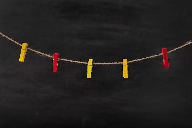 Pinces à linge rouges et jaunes sur corde sur fond noir. espace pour le texte, maquette.