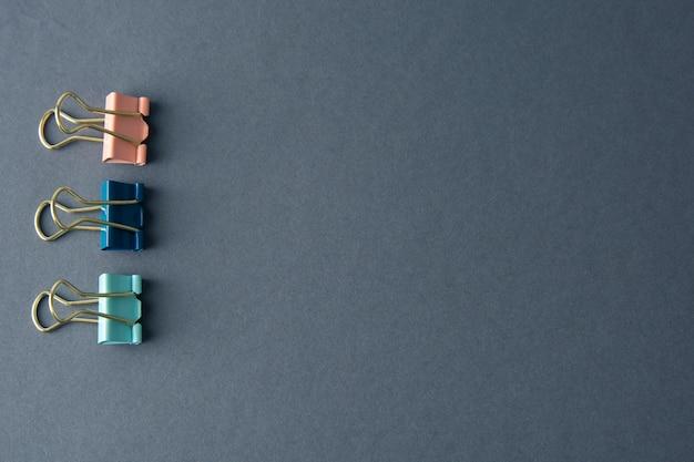 Pinces pour reliure colorul isolées sur fond gris, espace de travail, table de travail, espace copie.