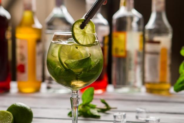 Pinces tenant une tranche de citron vert. boisson aux feuilles de menthe. cocktail hugo préparé par le barman. détendez-vous et prenez un verre.