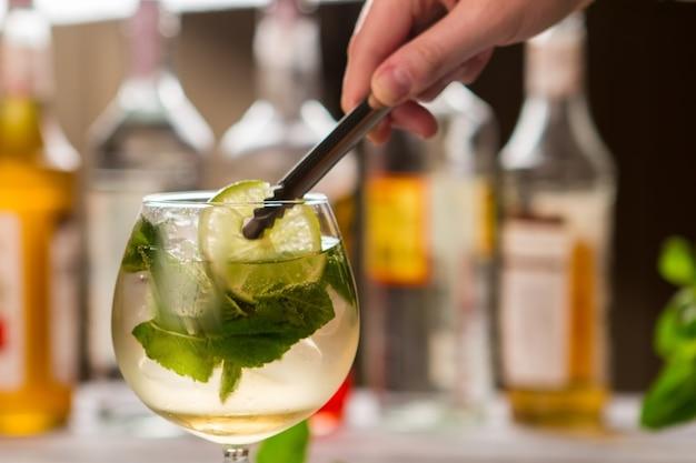 Les pinces tiennent une tranche de citron vert. feuilles de menthe en boisson. sirop sucré et jus aigre. cocktail hugo frais.