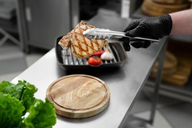Les pinces tiennent la viande cuite ail et tomate frits