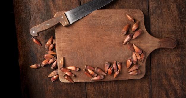 Pinhao, pignon, pin, araucaria brésilien, sur bois rustique avec un couteau, vue de dessus.