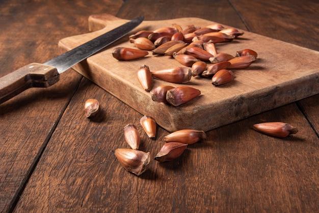 Pinhao, pignon, pin, araucaria brésilien, sur bois rustique avec un couteau