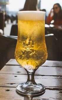 Pinte de bière en bouteille sur une terrasse. boisson à bulles transparente dorée. concept de détente et de détente entre amis