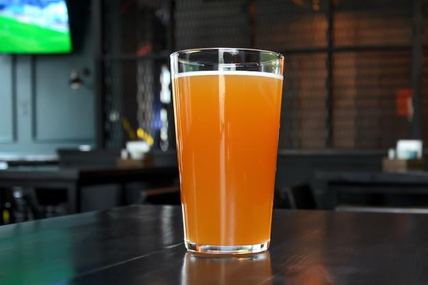 Pinte de fabrication de bière de blé légère sur table sombre à l'intérieur du bar des sports.