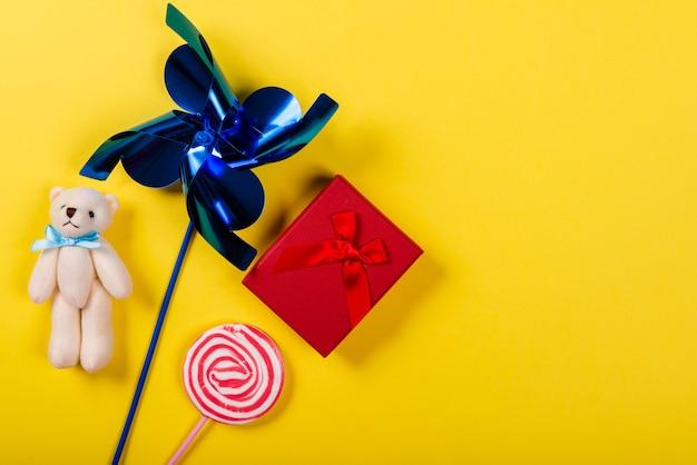 Pinwheel, ours en peluche, sucette et cadeau sur jaune