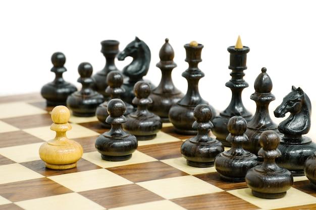 Un pion d'échecs blanc attaque des pièces d'échecs noires pièces d'échecs en bois à bord position du jeu d'échecs
