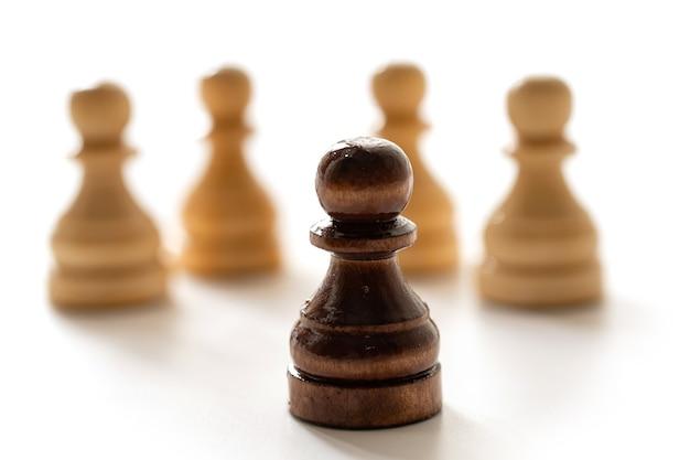Un pion d'échecs noir parmi les blancs. concept de racisme et de discrimination.
