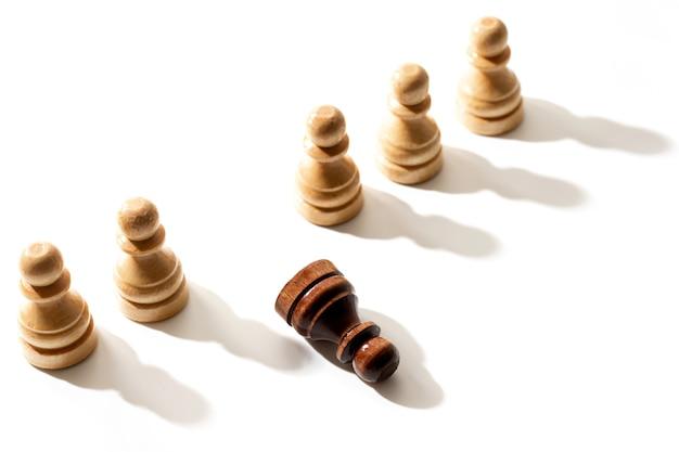 Un pion d'échecs noir se trouvant parmi les blancs. concept de racisme et de discrimination.