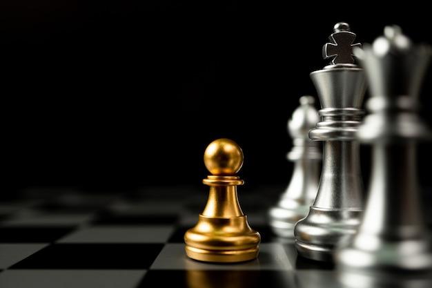 Pion d'échecs d'or debout devant d'autres échecs