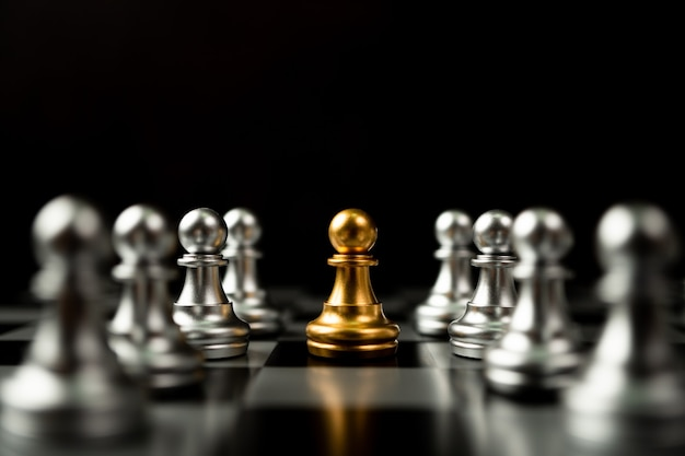 Pion d'échecs d'or debout pour être autour d'autres échecs