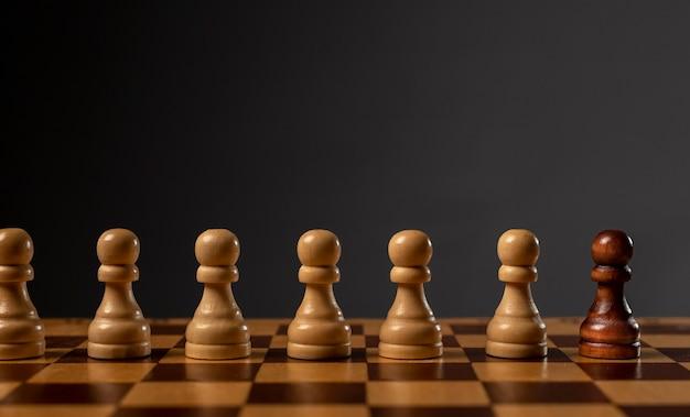 Un pion noir contre plusieurs autres. différent contre le concept de monopole et d'inégalité. copier l'espace