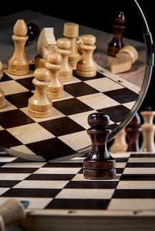 Le pion noir se regarde dans le miroir et voit un ensemble complet de pièces blanches, le concept de stratégie, de planification et de prise de décision, le concept de leader pour réussir