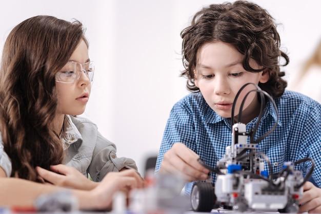Pionniers de la science talentueux. des enfants intelligents et astucieux impliqués assis à l'école et ayant une leçon de sciences tout en démontrant leurs compétences
