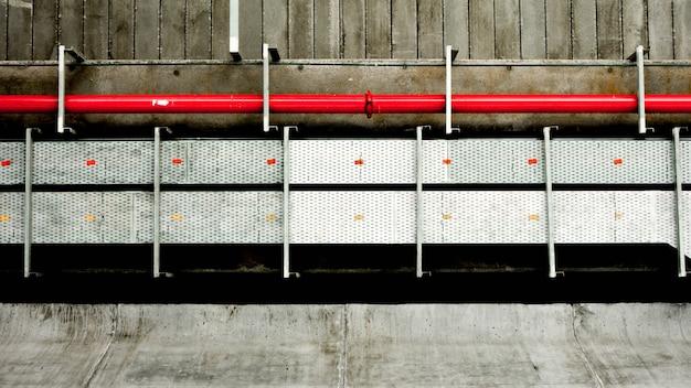 Pipe en acier rouge au bâtiment de ciment.