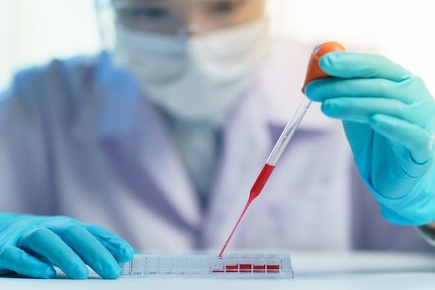 Pipeter en ajoutant du fluide aux tubes à essai. assistant de laboratoire analysant un échantillon de sang.