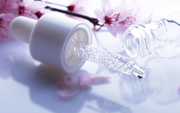 Pipette d'acide hyaluronique sur fond de fleurs