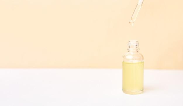 Pipette avec huile essentielle sur bouteille sur fond blanc et jaune. concept de médecine naturelle. aromathérapie