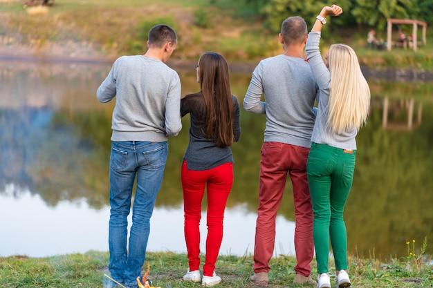 Pique-nique avec des amis dans un lac près d'un feu de joie
