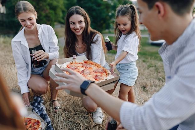 Pique-nique avec des amis mangeant de la pizza et buvant des boissons