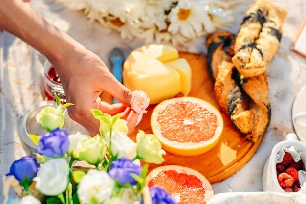 Pique-nique au coucher du soleil fruits, fromage et croissants sur nappe. prise de main de femme rose rose