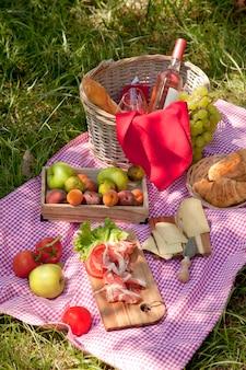 Pique-nique au parc sur l'herbe: nappe, panier, nourriture saine, vin rosé et accessoires