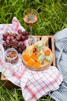 Pique-nique au parc sur l'herbe: vin, fromage et pain