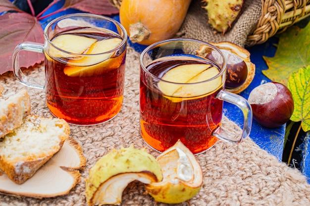 Pique-nique d'automne dans l'ancien parc avec thé chaud et gâteau. citrouille d'automne, châtaignes, pommes dans un panier et feuilles d'érable. vacances d'automne.
