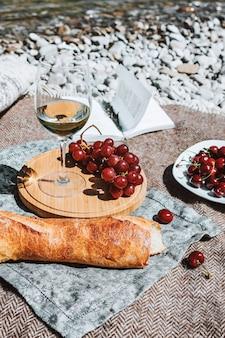 Pique-nique sur la côte avec verre de vin blanc baguette cerises raisin livre ouvert oreiller