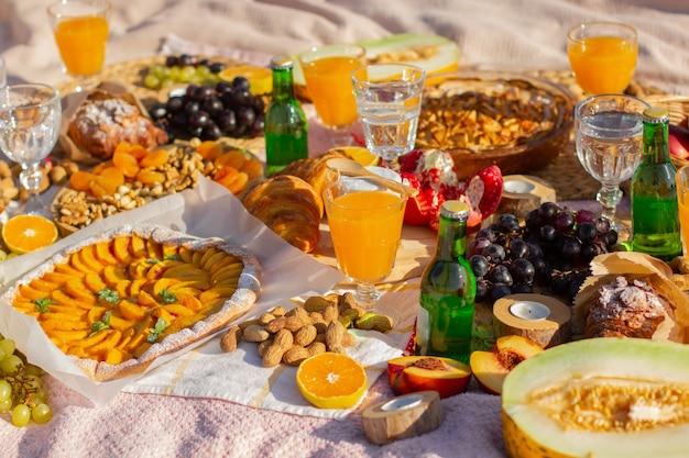 Un pique-nique dans le parc avec de beaux verres, fruits et pâtisseries.