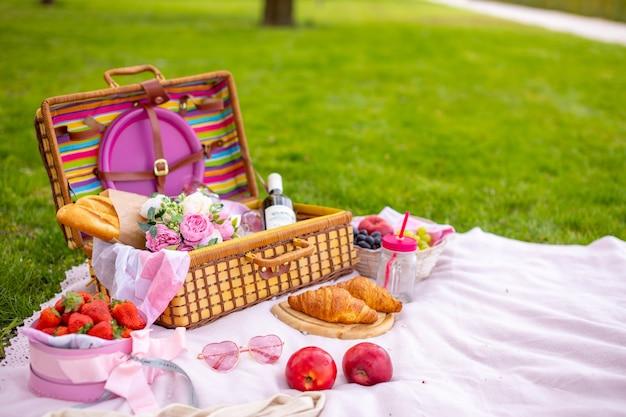 Pique-nique dans le parc sous les cerisiers en fleurs avec fruits, vin, pain et croissants