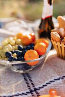 Pique-nique estival sur un tapis avec des fruits, du vin et du thé, des tasses, des croissants et des bonbons