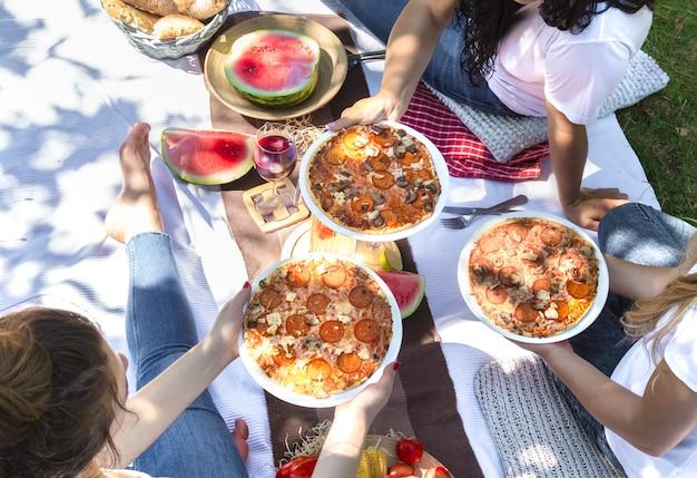Pique-nique d'été avec des amis dans la nature avec de la nourriture et des boissons.