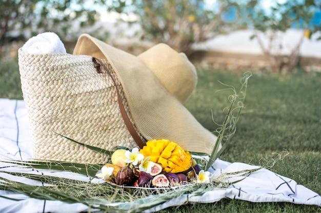 Pique-nique d'été avec une assiette de fruits tropicaux.