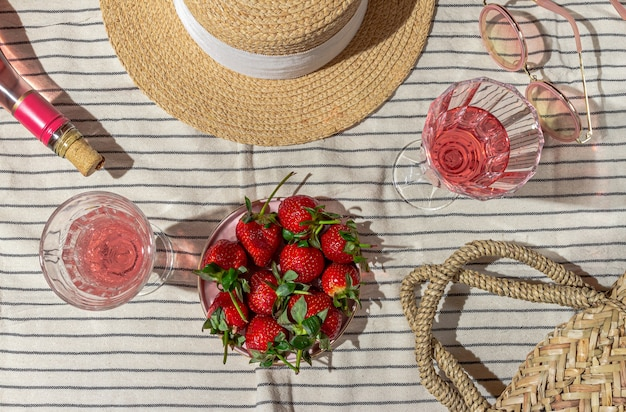 Pique-nique d'été avec champagne et fraises accessoires pour femmes sur un couvre-lit à rayures à plat