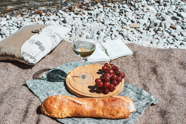 Pique-nique d'été sur la côte avec verre de vin blanc baguette cerises raisin livre ouvert oreiller