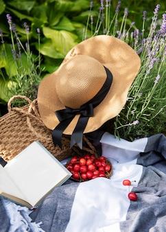 Pique-nique d'été dans le champ de lavande. pique-nique extérieur d'été de nature morte avec des baies, un chapeau de paille et un livre