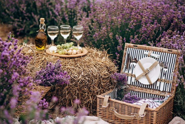 Pique-nique d'été dans le champ de lavande. verres de vin, panier pique-nique, collations et bouquets de fleurs sur une botte de foin parmi les buissons de lavande. mise au point sélective douce.